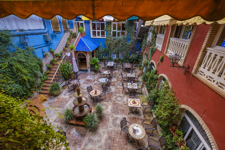 colorful courtyard terrace full of decorations and walls covered with plants