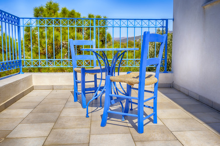 old greek blue chairs with wicker seating on a sun-drenched terrace at a vacation destination