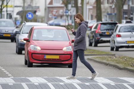 young woman walks on the crosswalk and checks her smartphone for messages and does not pay any attention to traffic. Imagens - 97422414