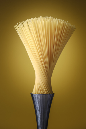 Spaghetti pasta as a modern design artwork on a steel pedestal and resembling a brush, food concept.