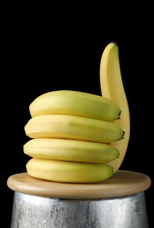 bananas lying on a wooden board in the shape of a hand with the thumb up, on a black background like us, healty food concept.