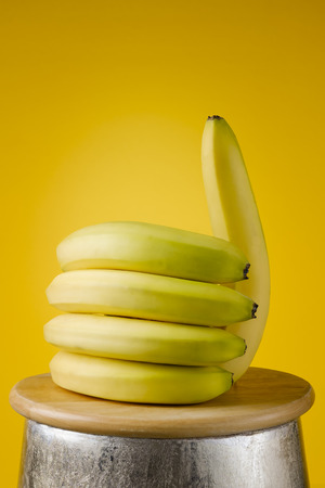 bananas lying on a wooden board in the shape of a hand with the thumb up, on a yellow background like us, healty food concept.