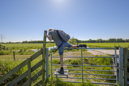 female hiker climbs over a gate with the help of a specially designed step for walkers in the polder landscape of the Netherlands on a summer day