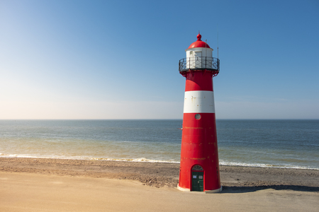 A red and white lighthouse at sea under a clear blue sky near Westkapelle in Zeeland, The Netherlands.