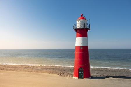 Ein rot-weißer Leuchtturm auf See unter einem klaren blauen Himmel in der Nähe von Westkapelle in Zeeland, Niederlande.