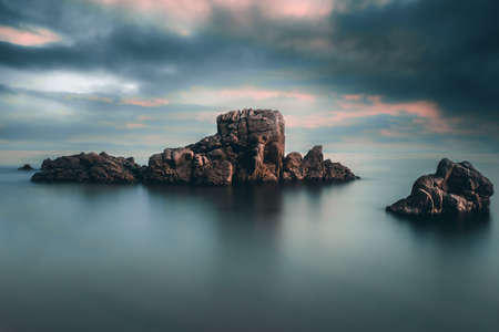 Beautiful long exposure against dramatic sunset sky on the beach with dragon rock and calm water