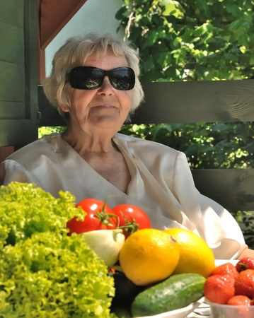 old lady - grandma in sunglasses on terrace in garden among fruit and vegetables Stock Photo - 8655563