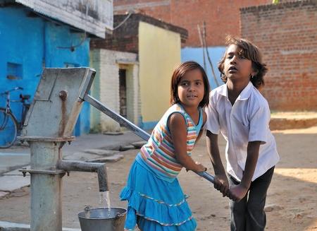pompe: Khajuraho, India - 27 novembre 2009 - Bambini pompare acqua nel secchio. In molte parti dell'India, senza acqua corrente nelle loro case.