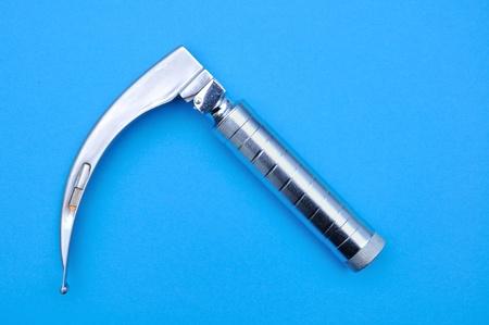 laryngoscope on blue background photo
