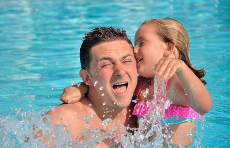 Father and daughter playing in the pool. photo