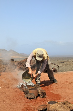 causing: Timanfaya National Park, Lanzarote, Spain - June 14, 2011 - Park worker pours water into the holes in the ground, causing an explosion of water up to several meters because of the hot volcanic ground.