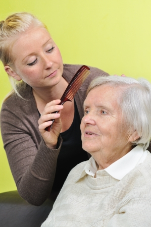 Senior woman with her caregiver in home  photo