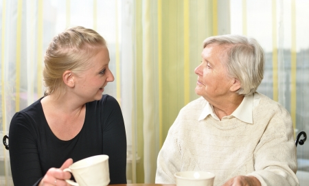 amigos abrazandose: Mujer mayor con su nieta hablan entre s�