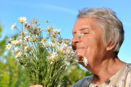 landlady: Senior woman smelling flowers on blue sky