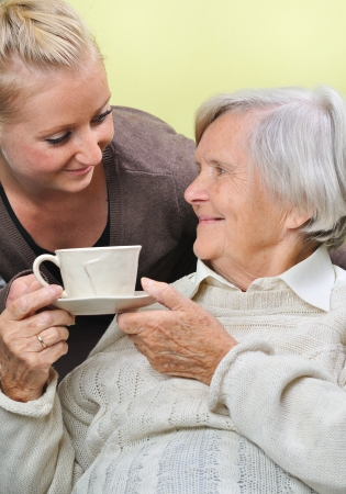 Senior woman with caregiver at home  photo