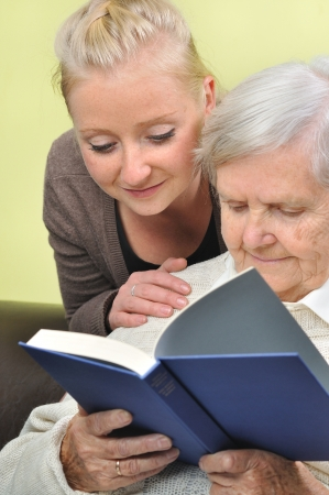 care at home: Senior woman with her caregiver in home reading book