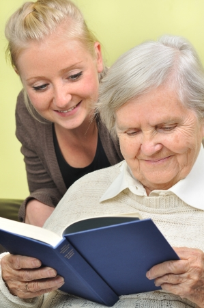 old age home: Senior woman with her caregiver in home reading book