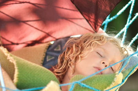 Child sleeps in a hammock in the garden  photo