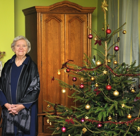 Elderly woman stands next to a Christmas tree in the room  photo