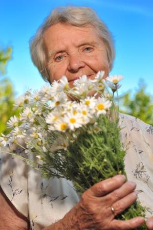 landlady: Senior woman smelling flowers on blue sky