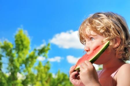 Lttle girl eating watermelon on the blu sky Stock Photo - 16303682