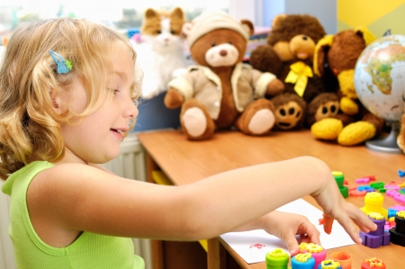 nursery room: Little girl painting hands in her room  Stock Photo