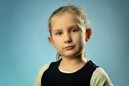 Portrait of a little girl on a blue background  photo