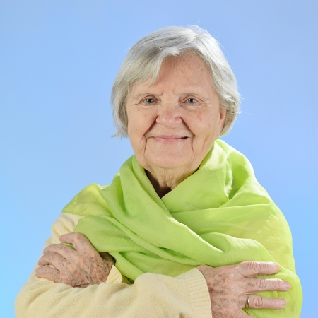 Senior happy woman with grey hairs against blue background  photo