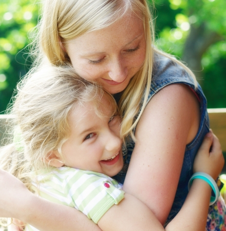 Young mother and daughter  Happy family in garden  photo
