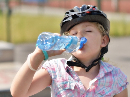 Young girl in a bicycle helmet drinking water  photo