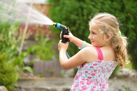 Young girl watering plants in the garden  Stock Photo