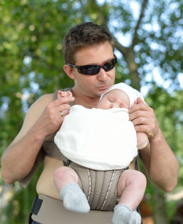 jointly: Happy father carries his baby in the carrier in sunny summer day