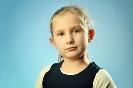 Portrait of a little girl on a blue  photo