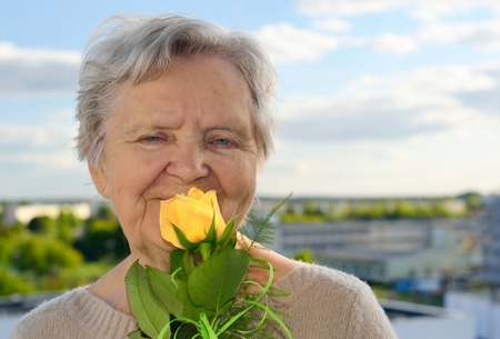 landlady: Senior woman smelling rose on blue sky