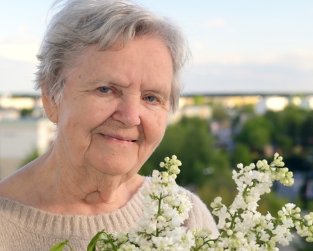 landlady: Senior happy woman with flowers  Stock Photo