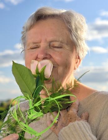 landlady: Senior woman smelling rose on blue sky
