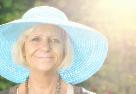Mature woman in blue hat in garden  photo