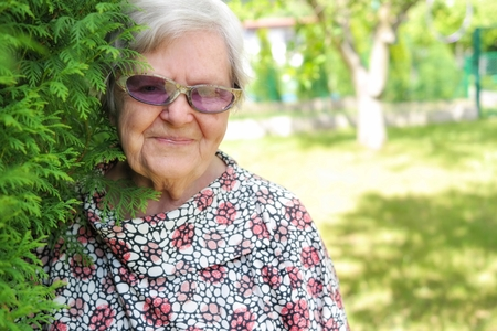 stay beautiful: Senior woman in sunglasses smiling in garden  Stock Photo