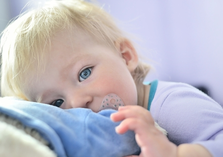 soother: Cute baby with blue eyes hugging a mascot  Stock Photo