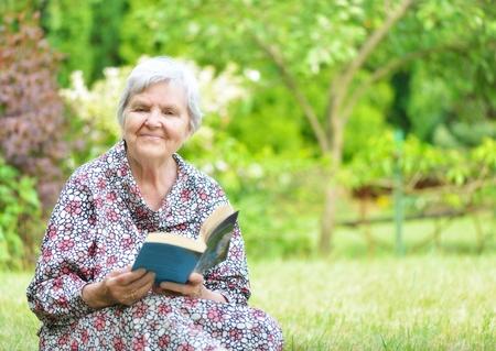 Senior woman reading book in park  photo