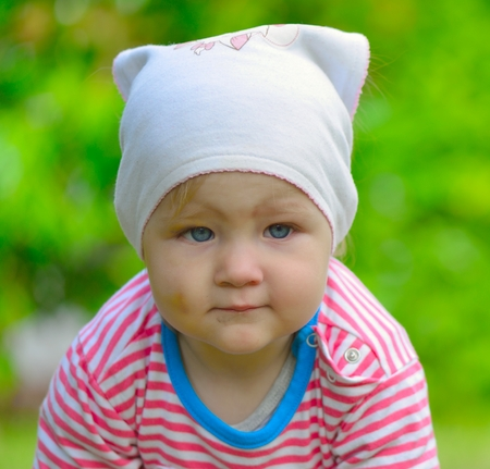 Baby in a scarf on her head walking toward the camera  photo