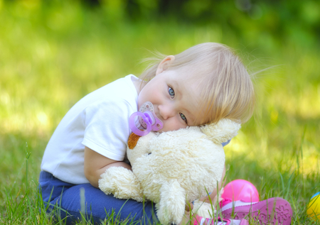 Cute baby with blue eyes hugging a mascot  photo