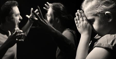 niño llorando: Niño reza por la paz en la familia en el fondo de reñir a los padres.