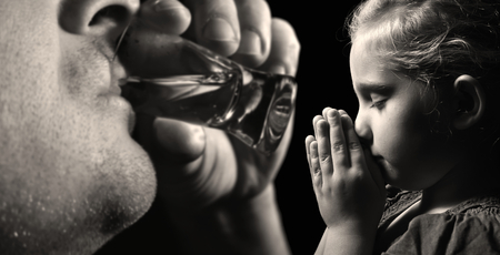 drunk girl: Child prays that father stopped drinking alcohol. Stock Photo