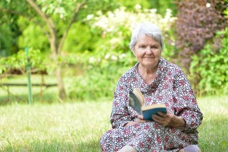 Senior woman reading book in park. photo