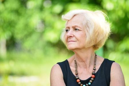 Mature, blonde woman in garden, Stock Photo - 31727538