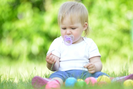 teat: Cute baby playing on grass in garden. Stock Photo