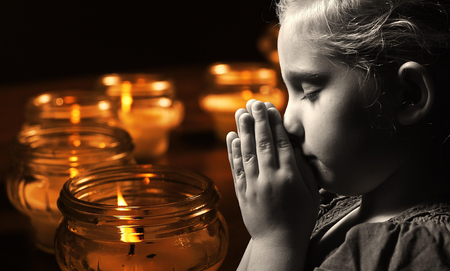 child praying: Praying child with candles on background.