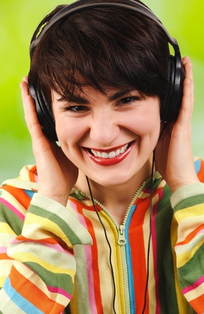 Young attractive brunette listens to music through headphones on a green background. photo