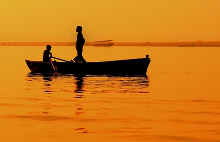 remoteness: Two boys in  boat on Ganges. Varanasi in India.